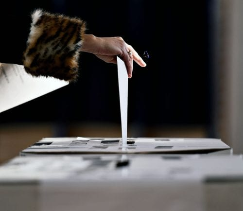 Someone casting a vote by putting their ballot in the box