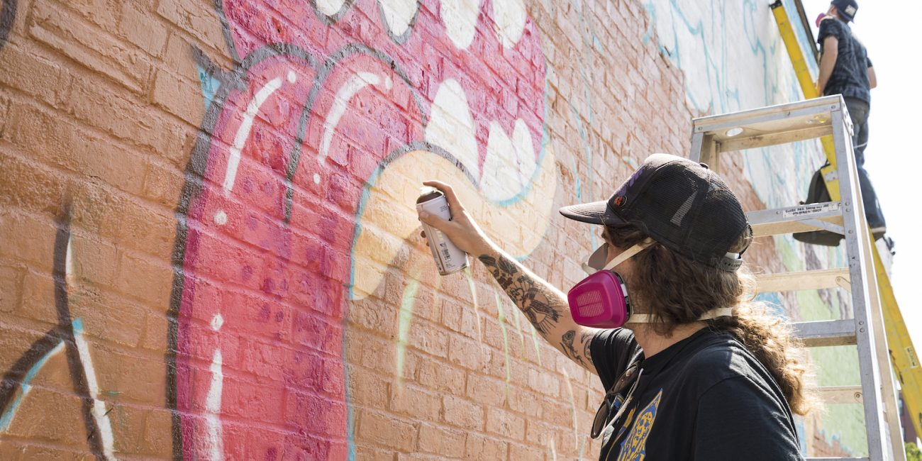 Artist Tallboy adds details to the mouth of the monster in his and Brian Denahy's mural on Washington Street.