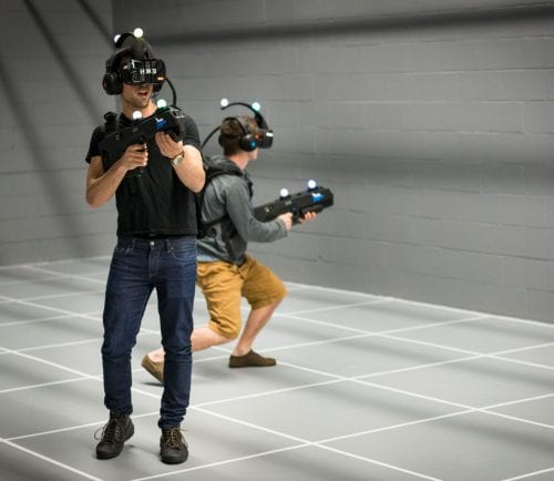 Two men walk with VR headsets and fake guns