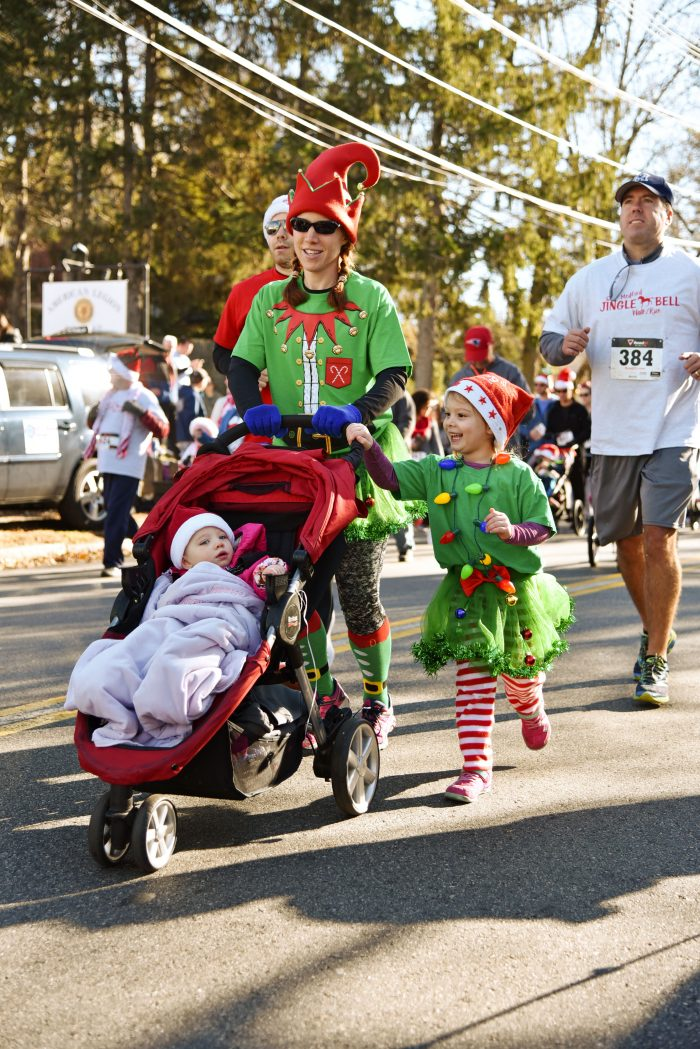 A family dressed as Christmas elves begins the race down Winthrop Street during the fifth annual Jingle Bell 5K Run/Walk on November 25 to raise money for Medford schools.
