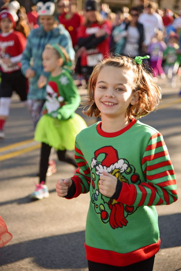 Lila Bushey, 8, happily participated in the Jingle Bell Run/Walk wearing a Grinch sweater.