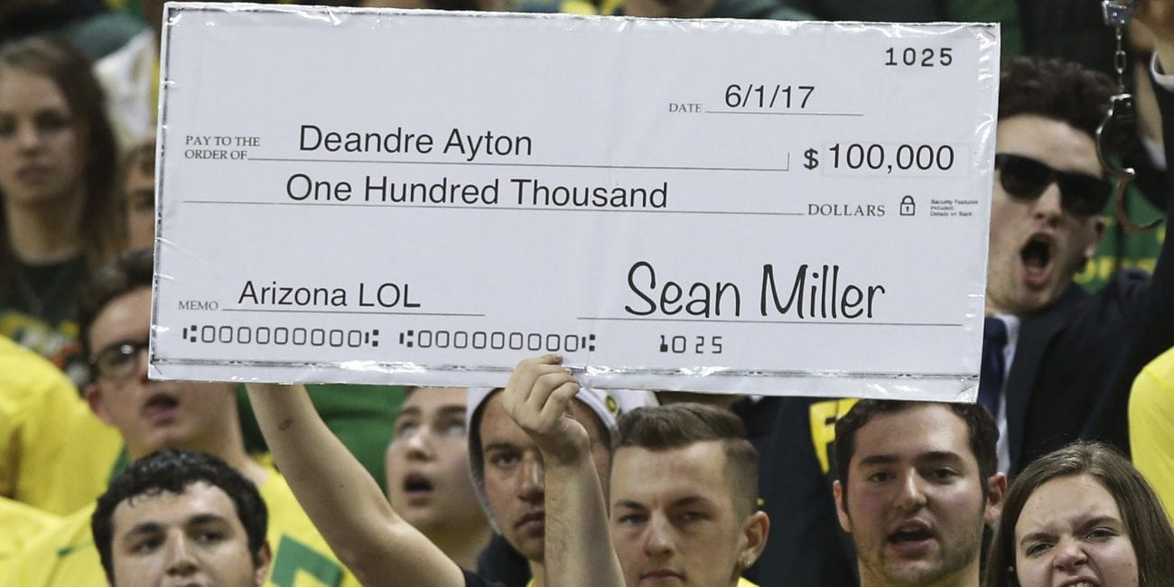 Fans in the Oregon student section hold up a sign making fun of the controversy surrounding Arizona head coach Sean Miller during the first half of an NCAA college basketball game Saturday, Feb. 24, 2018, in Eugene, Ore. (AP Photo/Chris Pietsch)