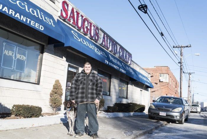 Saugus Auto-Craft Inc., Shop and Appraisals Manager Lenny Spallone Jr., stands with his dog Teako in front of his father's shop on Bennett Street in Lynn.