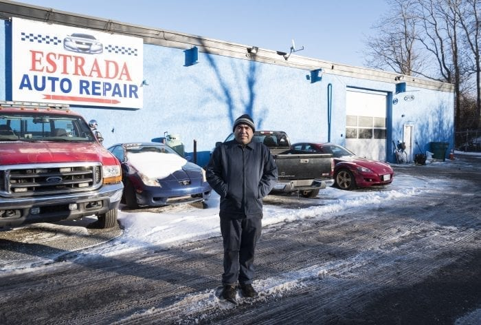 Carlos Estrada, owner of Estrada Auto Repair in Lynn, stands in front of his shop on Bennett Street.