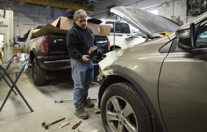 vEo Autobody Solutions & Repair Llc., Manager Alfredo Chavez works on an SUV that had its front end damaged in an accident.