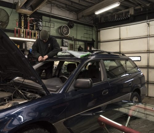 Bennett Street Tire & Glass glass technician Steve Boyd works to replace the windshield of a Subaru Outback.