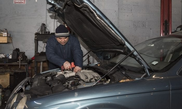 Carlos Estrada, owner of Estrada Auto Repair, works on the engine of a car in his shop on Bennett Street in Lynn.