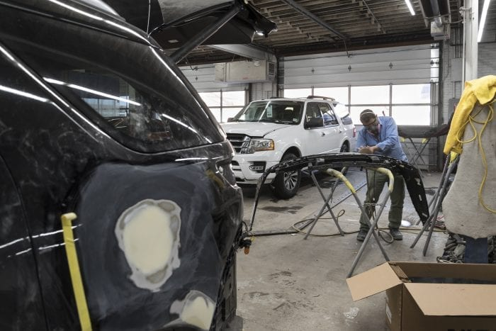 Having filled a dent with bondo, Salvador Reyes takes a sander to the bumper of a damaged SUV so he can smooth out his repair and prepare the bumper for paint at Saugus Auto-Craft Inc., on Bennett Street in Lynn.