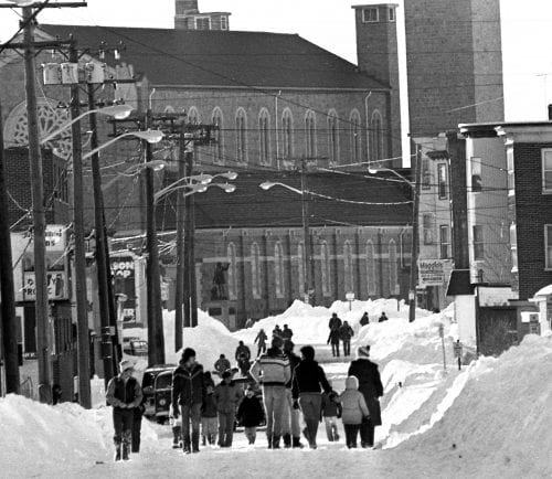 Residents walk down the center of a barely plowed Revere Street in the days after the Blizzard of '78.