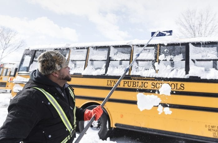 Bryan Perez of Lynn, a member of the snow clearing crew that NRT Buses sent out on Wednesday morning, works to clear Lynn school buses in preparation for school on Thursday.