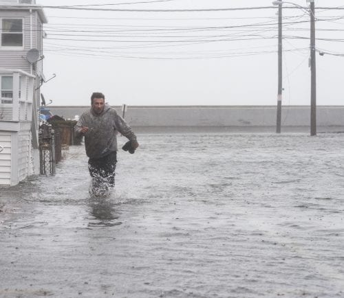Nick Marazzi of East Boston wades through the flood waters on Pearl Avenue in Revere as he makes his way back to his truck.
