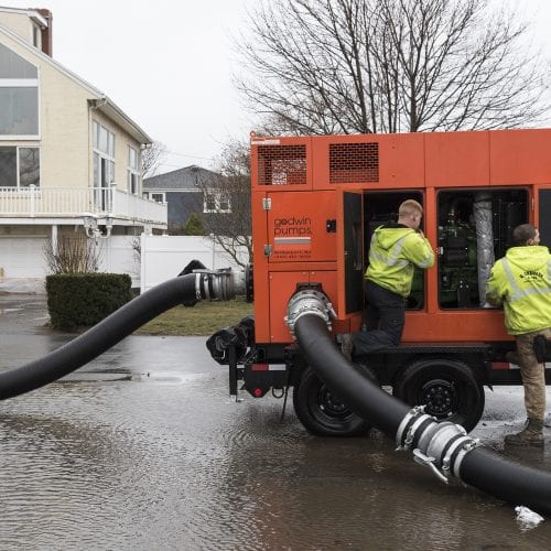 N. Granese & Sons General Contractors employees Jon McCarriston of Haverhill, left, and Bill Chalmers of Rockport work to get a pump going to remove water from Ward Road in Nahant.