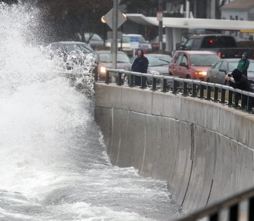 Wave watchers along Lynn Shore Drive take videos and photos as each wave rolls in at high tide.