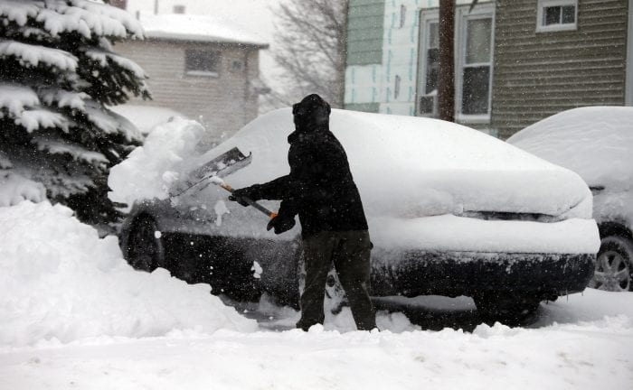 Johnson Cano clears a path to his car at his Chestnut home during Tuesday's storm.