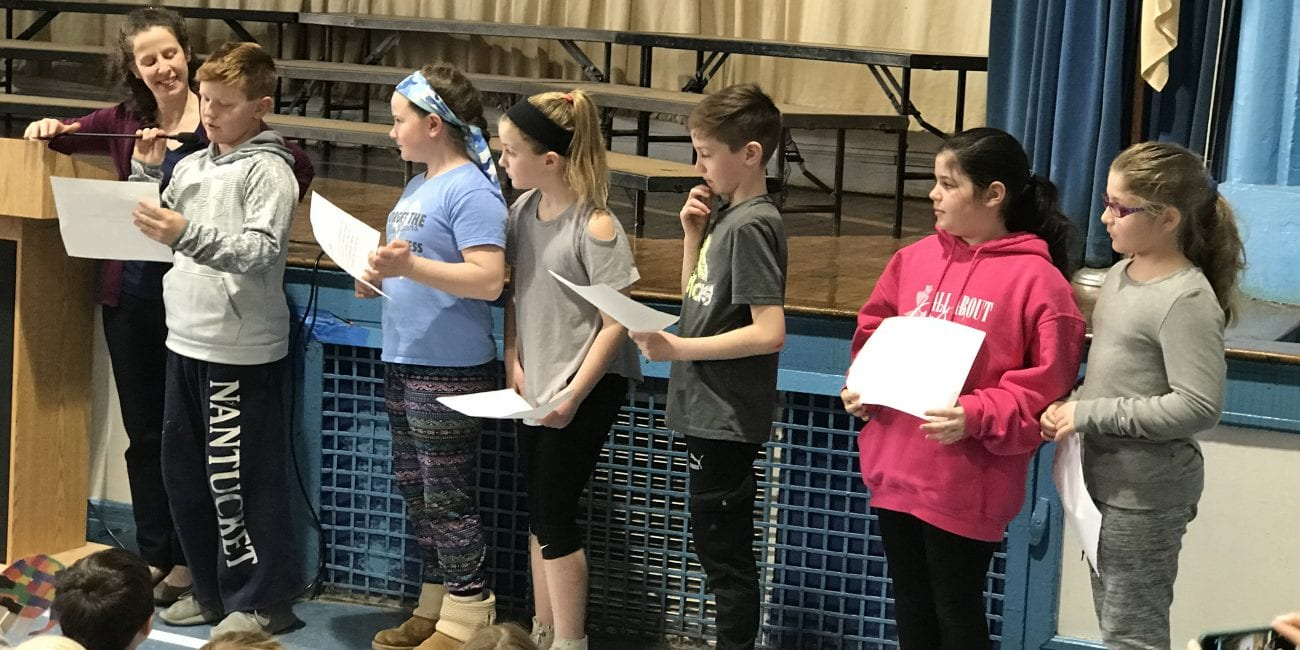 Third graders Max Battinelli (left), Victoria Pierro, Jane Raymond, Bogdan Lutic, Lila Schwartz and Sophia Zanni present their acts of kindness during a school-wide assembly to wrap up Hadley School's Great Kindness Challenge.