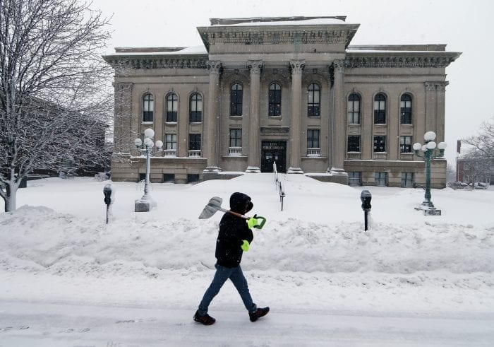 Lynn, MA—Tue March 13, 2018—Ryan Hernandez of Lynn walks past the closed Lynn Public Library to do some shoveling in downtown Lynn. The storm forced the Library to close for the day.