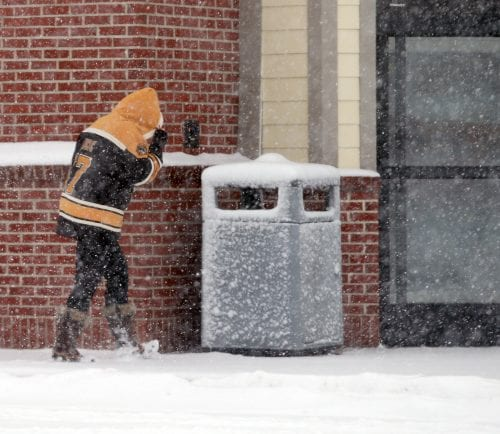 Lynn, MA—Tue March 13, 2018—Shopper at CVS on Boston Street Lynn shields face from blowing snow during the Tuesday storm.