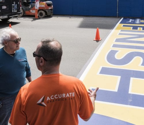 Accurate Graphic Inc. owner Peppy Bolognese, left, and employee Anthony Bisenti speak at the 122nd Boston Marathon finish line, having finished laying it out on Boylston Street in Boston on Thursday.