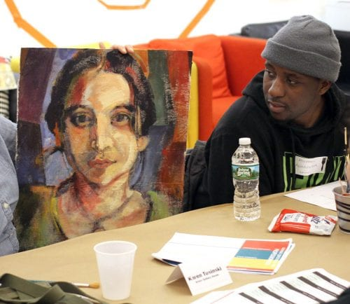 Karen Tusinski talks to Sydney Field, right, about careers in art and design using a painting by Michael Aghahowa, left, as an example at the art and design table during career night at Raw Art Works.