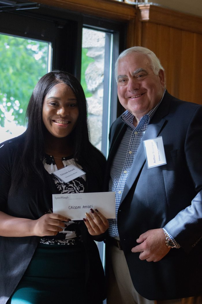 Chisom Amadi, left, of Lynn and a senior at Pioneer Charter School of Science II in Saugus, receives a scholarship from YMCA committee member Arthur Bourque III.