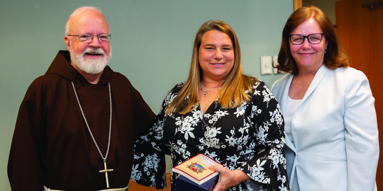 Andrea Alberti, center, with Cardinal Seán O'Malley and Kathy Mears, superintendent of the Archdiocese of Boston Catholic schools.