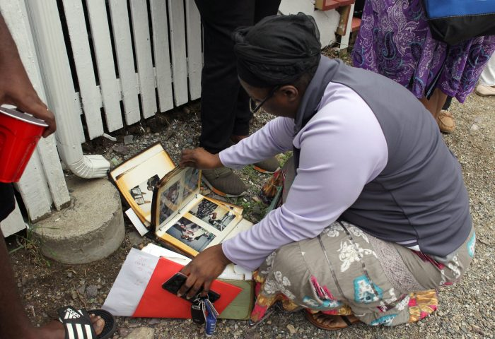 Lynn, MA--Fri May 4, 2018--Shirley Saintvil checks through a charred family photo album that was saved by firefighters at a two-alarm fire at 15 Dorinda Circle shortly before Friday morning.