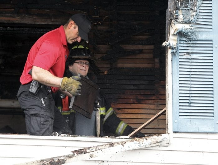 State Police fire investigator Mike Sweet (red shirt, left) and Lynn fire investigator Lt. Mike Smith (in uniform, right) comb through debris at a two-alarm fire at a two-family home at 15 Dorinda Circle that broke out shortly before 9 a.m. Friday morning.