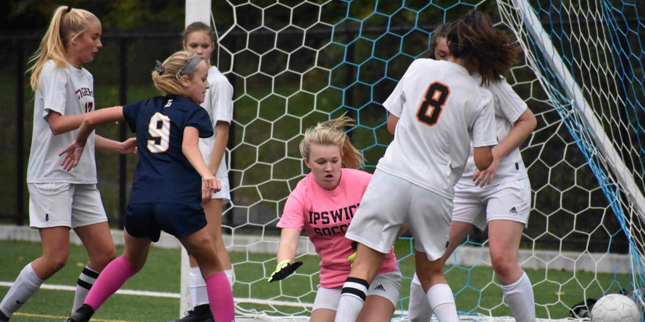 Abby Lucich (9) watches her shot go past Ipswich goalie Cayla Greenleaf for  her first of three goals as the Tigers' Cate Phypers (8) tries to defend.