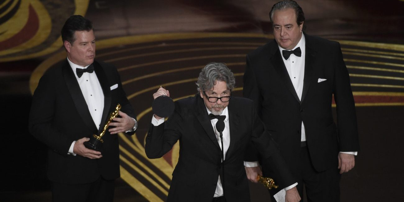 """From left; Brian Hayes Currie, Peter Farrelly and Nick Vallelonga accept the award for best original screenplay for """"Green Book"""" at the Oscars on Sunday at the Dolby Theatre in Los Angeles."""