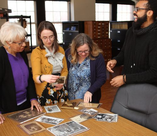 Lynn, Ma. 2/13/19. From left to right: Iris Kimber, Judith Marhsall, Sue Walker, and Richard Valentine look through photographs that will be part of the Untold Stores Exhibit at the Lynn Musuem this summer.