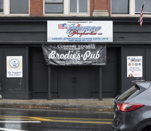 A pedestrian walks past the future site of Brodie's Pub on Main Street in Peabody.