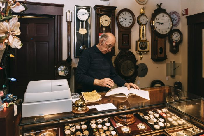 George Phillips looks up information on a watch as he stands behind the counter of his shop.