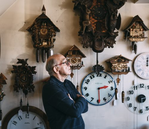 George Phillips, surrounded by clocks, looks out the front window of his shop, Phillips' Clock Shop, in Swampscott.
