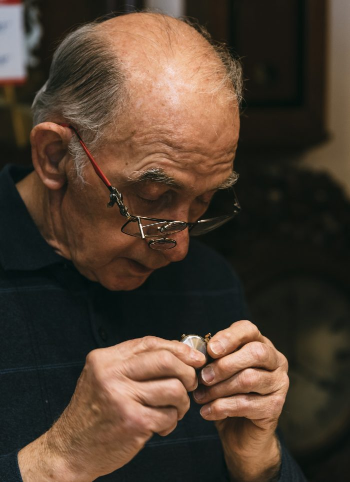 George Phillips inpects the band of a watch brought into his shop by Julia Babushkina of Nahant.