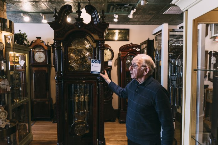 George Phillips speaks about one of the grandfather clocks in his shop.
