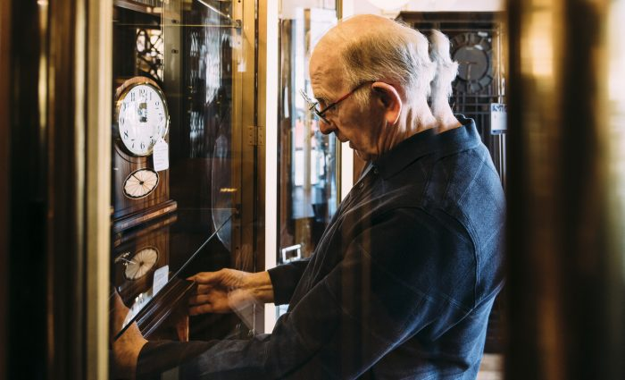 George Phillips inspects clocks in one of his display cases.