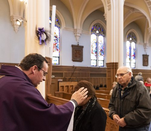 Parishioners receive their ashes from Fr. Robert Poitras during Mass on Ash Wednesday at St. Pius V Church.