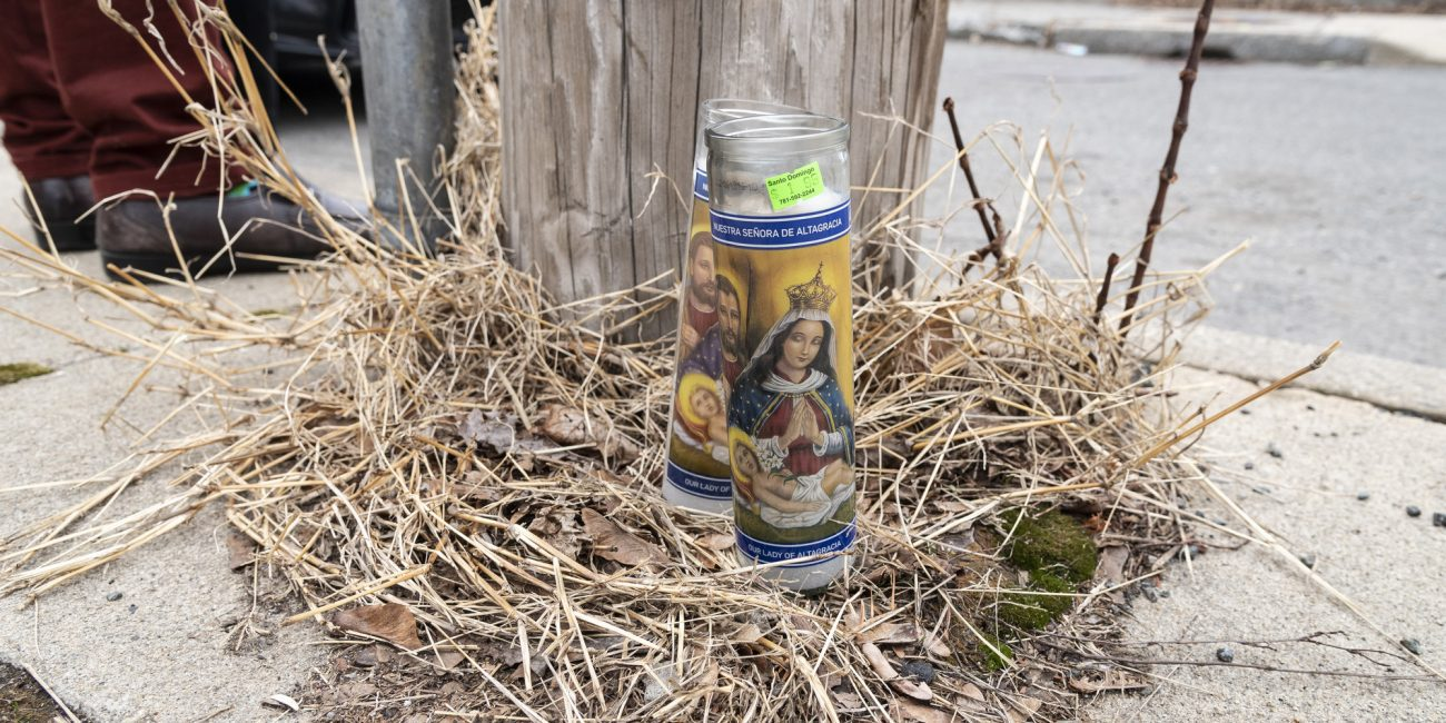 Prayer candles rest at the base of a telephone pole on Williams Avenue in Lynn where Anthony Betancourt was shot and killed early Wednesday morning.
