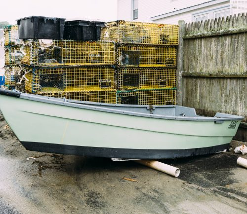 A dory sits next to fishing traps at the Swampscott Fish House.